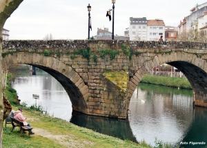 señora leyendo junto al río Gabe. Foto Figaredo, Gijón