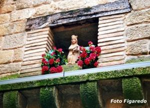 virgen en ventana con flores